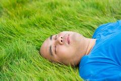 Fetter Mann, der auf dem grünen Gras liegt, um sich zu entspannen Lizenzfreie Stockbilder