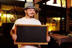 Ein fetter netter Mann in einem bayerischen Hut mit einer Feder während der Feier von Oktoberfest hält ein Zeichen oder eine Tafe stockfotografie