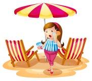Ein fettes Mädchen, das einen Saft nahe dem Strandschirm mit Stühlen hält Lizenzfreies Stockbild