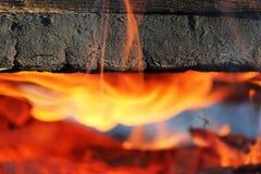 Ein Feuer, in dem alte gemalte Bretter im Feuer eingeschlagen werden Stockfoto