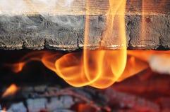 Ein Feuer, in dem alte gemalte Bretter im Feuer eingeschlagen werden Stockfotografie