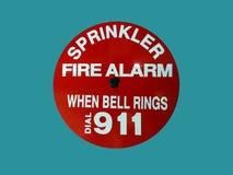 Ein Feuermelder auf einer informierenden Wand, dass eine Berieselungsanlage funktioniert, wenn die Glocke schellt Lizenzfreie Stockfotografie