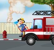 Ein Feuerwehrmann, der ein Feuer nahe der Straße rettet Stockfotografie