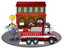 Ein Feuerwehrmann, der einen Wasserschlauch neben einem Löschfahrzeug hält Lizenzfreie Stockfotos