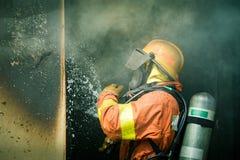 Ein Feuerwehrmannwasserspray durch die Hochdruckdüse, zum von surrou abzufeuern Stockfotografie