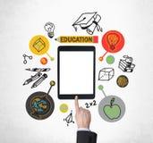 Ein Finger betätigt den Knopf auf der Tablette mit leerem Bildschirm Pädagogische Ikonen werden um die Tablette gezeichnet Stockfoto
