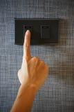 Ein Finger dreht einen Lichtschalter Lizenzfreie Stockfotografie