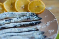 Ein Fisch gerollt in den Mehllügen auf einer beige Platte lizenzfreie stockbilder