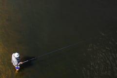 Ein Fischer auf dem Ufer fischt mit einer Angelrute Lizenzfreie Stockfotografie