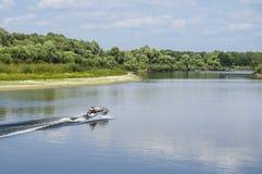 Ein Fischer auf einem Motorboot reitet den Fluss stockbilder