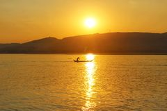 Ein Fischer bei Sonnenuntergang auf dem Irrawaddy stockbild