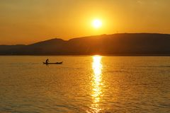 Ein Fischer bei Sonnenuntergang auf dem Irrawaddy stockbilder
