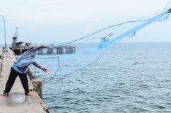 Ein Fischer, der sein Netz vom Boot wirft Lizenzfreie Stockfotos