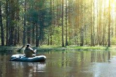 Ein Fischer in einem Boot auf dem Fluss lizenzfreies stockbild