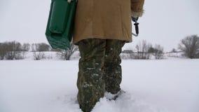 Ein Fischer geht auf einen schneebedeckten See auf der Suche nach einem guten Fischereiplatz stock video