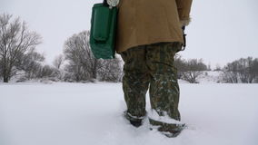 Ein Fischer geht auf einen schneebedeckten See auf der Suche nach einem guten Fischereiplatz stock footage