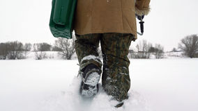 Ein Fischer geht auf einen schneebedeckten See auf der Suche nach einem guten Fischereiplatz Stockbild