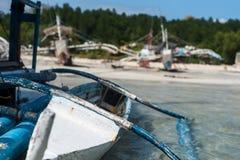 Ein Fischerboot, das im seichten Wasser durch den Strand sich lehnt Stockfotografie