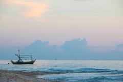 Ein Fischerboot mit Seestrandsonnenaufgang Stockfotos