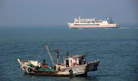 Ein Fischerboot und die Fähre Stockbilder
