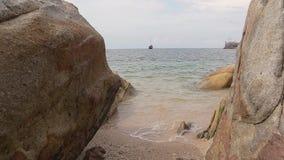 Ein Fischerboot weit weg in dem Meer bei der Gestaltung der Felsen stock footage