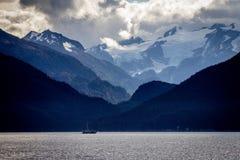 Ein Fischereifahrzeug in einer enormen alaskischen Landschaft Stockfotos