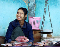 Ein Fischhändlerverkauf einige Fische mit traditionellen Skalen im nassen Markt am 4. Januar 2011 im bagan Markt, Myanmar Stockbild