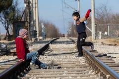 Ein Flüchtlingskind sitzt auf der Eisenbahn nahe der Grenzüberschreitungswette Stockfoto
