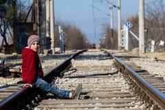 Ein Flüchtlingskind sitzt auf der Eisenbahn nahe der Grenzüberschreitungswette Lizenzfreie Stockbilder