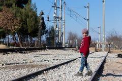 Ein Flüchtlingskind sitzt auf der Eisenbahn nahe der Grenzüberschreitungswette Stockbilder