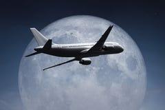 Ein Flugzeug und der Mond Lizenzfreie Stockfotos