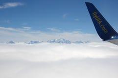 Ein Flugzeugflügel über Wolken Stockbilder