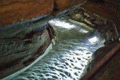 ein Fluss in einer Stalaktithöhle ist gehende Abflussrinne stockfoto