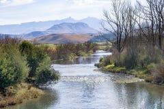 Ein Fluss läuft durch die Vorberge des die Drachenberge-Gebirgszugs bei Underberg in Südafrika stockfotos