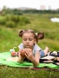 Ein Foto eines kleinen Mädchens, das auf eine Decke legt und ein Picknick hat Stockfoto