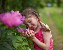 Ein Foto eines kleinen Mädchens, das große helle Blumen mit ihren Augen riecht, schloss Lizenzfreies Stockfoto