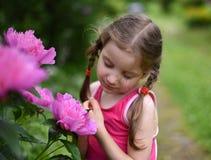 Ein Foto eines kleinen Mädchens, das große helle Blumen mit ihren Augen riecht, schloss Lizenzfreie Stockfotos