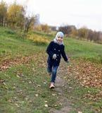 Ein Foto eines lächelnden kleinen Mädchens, das auf einem Weg in einem Herbstpark läuft Stockfotos