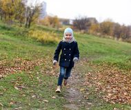 Ein Foto eines lachenden sorglosen kleinen Mädchens, das auf einem Weg in einem Herbstpark läuft Lizenzfreie Stockfotos
