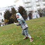 Ein Foto eines lachenden sorglosen kleinen Mädchens, das auf einen Weg in einem Herbstpark springt Stockfoto