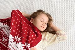 Ein Foto eines schönen kleinen Mädchens in einer gestrickten roten Kappe und in einem großen angenehmen Schal schlafend auf einem Stockfoto