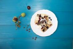 Ein Foto von zwei Wiener Oblaten, gegossen mit Schokolade mit Beeren und Eiscreme auf einem Holztisch auf den Brettern Kastanien, Lizenzfreies Stockbild