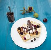 Ein Foto von zwei Wiener Oblaten, gegossen mit Schokolade mit Beeren und Eiscreme auf einem Holztisch auf den Brettern Kastanien, Stockfotos