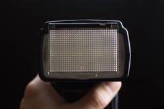 Ein Fotograf, der eine Kamera mit Blitz gegen schwarzen Hintergrund hält Lizenzfreie Stockfotos