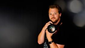 Ein Fotograf hält seine Kamera Stockbild