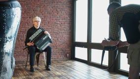 Ein Fotograf macht Fotos eines Musikers mit einem Akkordeon stock footage