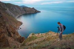 Ein Fotograf mit einem Stativ und einer Kamera Lizenzfreie Stockfotos