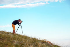 Ein Fotograf mit einem Stativ und einer Kamera macht Fotos Lizenzfreie Stockfotografie