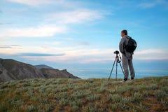Ein Fotograf mit einem Stativ und einer Kamera macht Fotos Stockbilder