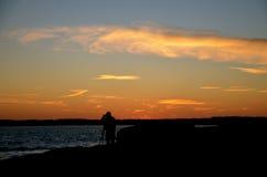 Ein Fotograf nimmt den Ozean gefangen, während die Sonne einstellt Lizenzfreies Stockfoto